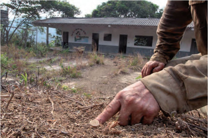 Photo 1: A farmer shows a landmine on the playground of the local school in the village of La Mirandita. (©Jesus Abad Colorado 2010, with kind permission from Nubia Bello)