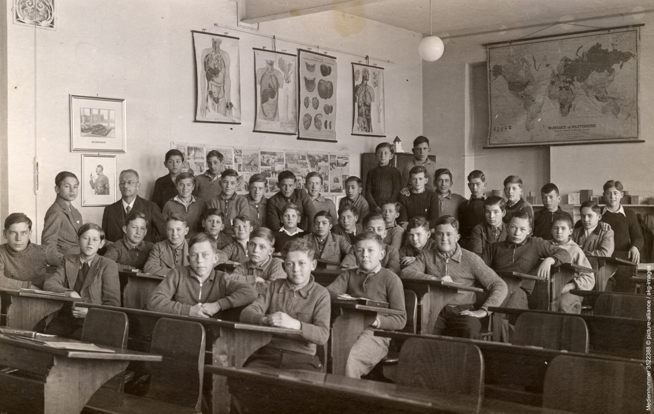 """Figure 7: Photo of an alleged Jenaplan school during the Nazi dictatorship. Notes (by Hein Retter): 1/The photo obviously does not show a Jenaplan school. 2/""""Jena-Plan model schools"""" did not exist in the NS state. 3/The description of the photo (""""Mediennummer 3522388 © picture-alliance / akg-images"""") by """"dpa Picture-Alliance GmbH"""" is: Boys' class with teacher in the classroom, photo, without place and year (Germany, 1935); see also: Heinemann (2010)."""
